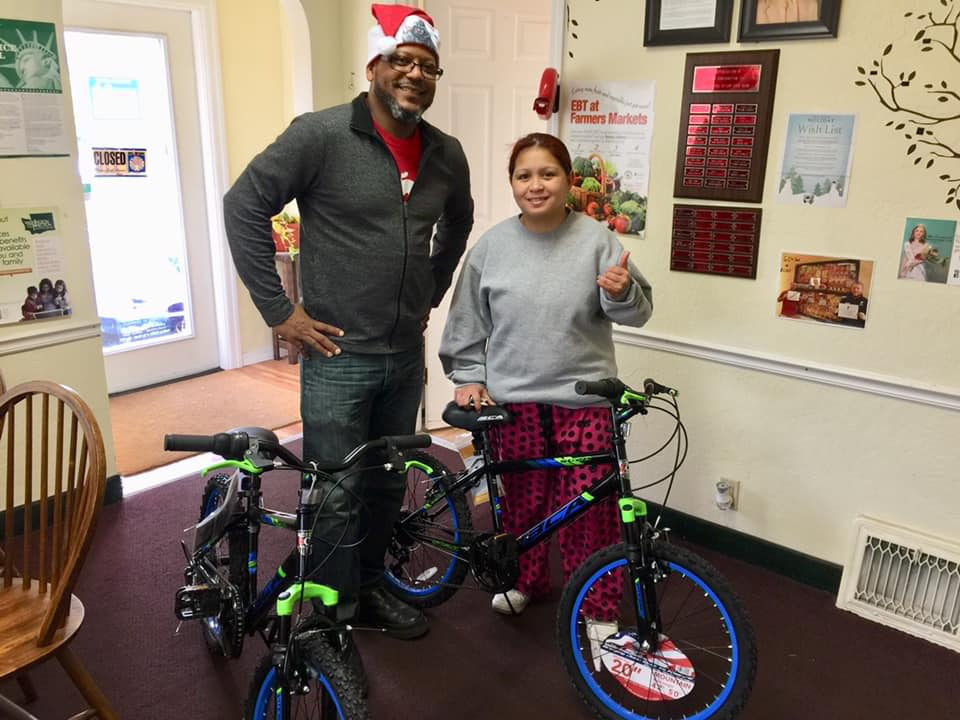 Chris gives a client two boy's bikes for her sons.
